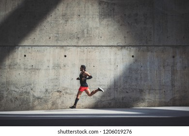 Muscular male athlete sprinter running fast against gray concret background