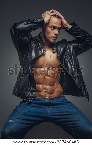 23d059ac384 Muscular male in blue jeans and black jacket wearing on shirtless body.  Isolated on grey background. - Image