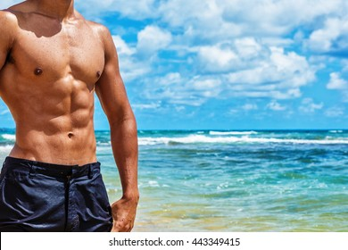 Muscular male body builder torso on a sunny day at the beach