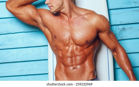 Muscular male body on blue background.