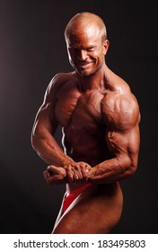The muscular male bodybuilder flexing biceps on black background