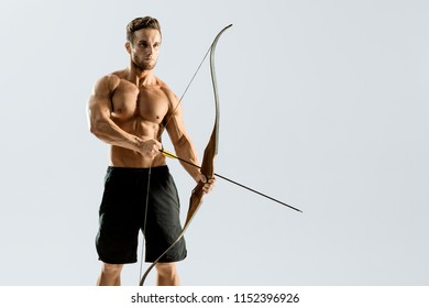Muscular male with bow and arrow on white background. Strong man with naked torso. Sport, workout, target and motivation.