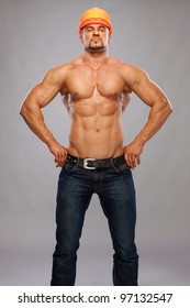 Muscular male builder on gray  background