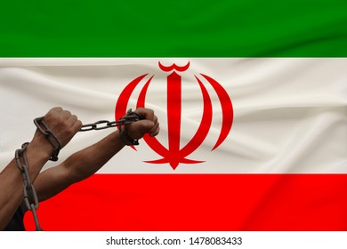 muscular male hands wrapped in a thick iron czar against the background of the state flag, the concept of political struggle, crime, cruelty, imprisonment, violation of human freedom