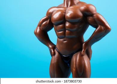 Muscular male mannequin nude torso. Bodybuilder doll on blue background.