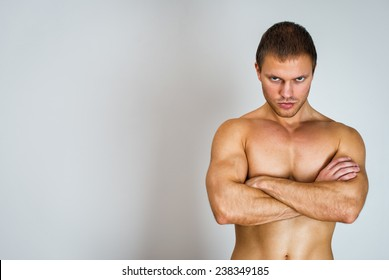 Muscular male model with arms folded. Place for text.