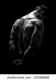 Muscular male model bodybuilder preparing for fitness training, turned back. Studio shot on black background. Black and white photo.