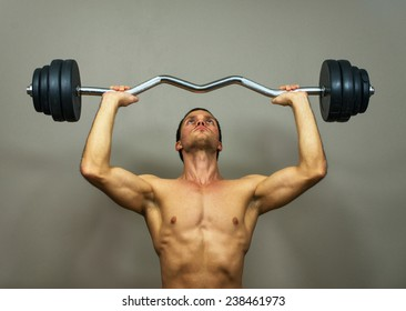 Muscular male model doing exercises with barbell.