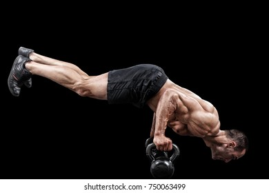 Muscular male practicing push ups in front of black background