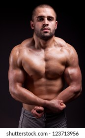 Muscular male showing muscles isolated on black background