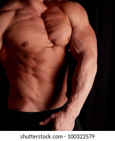 Muscular male torso of bodybuilder on black background