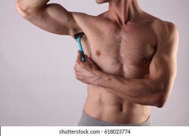 Muscular male torso close up , chest and armpit , underarm hair removal. Male depilation. Young attractive muscular man using razor to remove hair from his body