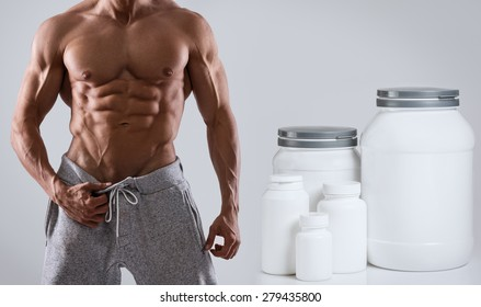 Muscular male torso and different food supplements