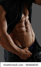 Muscular male torso, shirt and jeans. Gray background.