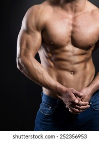 muscular male torso with six pack of a fit bodybuilder in jeans on black background.