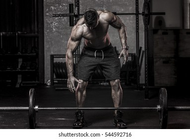 muscular man in about to pickup barbell