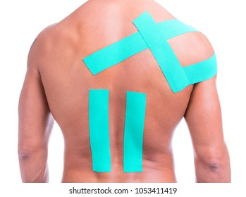 Muscular man with adhesive tape on shoulder and back for physiotherapy treatment, isolated on a white background
