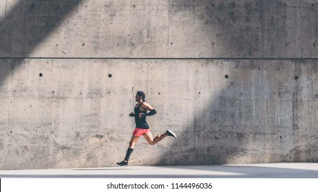 Muscular man athlete sprinter running fast,exercising outdoors,jogging outside against gray concret background with copy space area for text message or ad content.Side view,full length