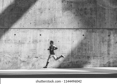 Muscular man athlete sprinter running fast,exercising outdoors,jogging outside against gray concret background with copy space area for text message or ad content.Side view,full length.Black white