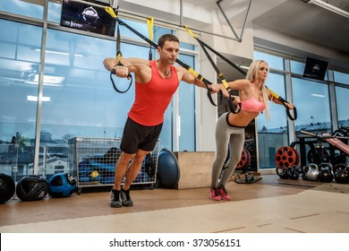 Muscular man and athletic woman doing exercises with expander in a gym.