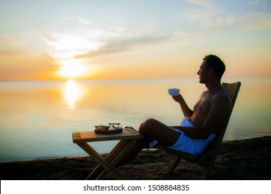 the muscular man bare-chested and in a towel drink coffee near the beach at sunset.