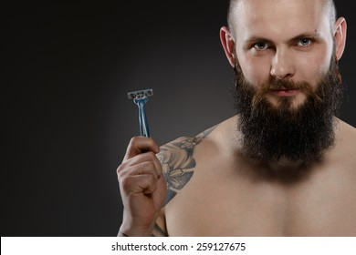 Muscular man with a beard holding a razor - gray background