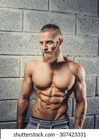 Muscular man with beard showing his great body over grey background.