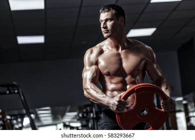 Muscular man bodybuilder training in gym and posing muscle