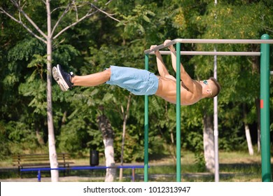 Muscular Man Does A Horizontal Pull On Bar In City Park