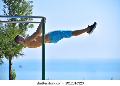 Muscular Man Does A Horizontal Pull On The Bar On a Blue Sky Background
