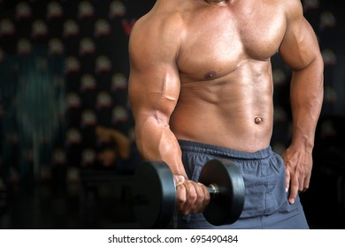 Muscular man doing a barbell bicep curl in a gym.