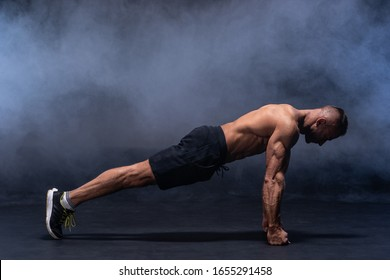 Muscular man doing calisthenic exercise isolated on the black background