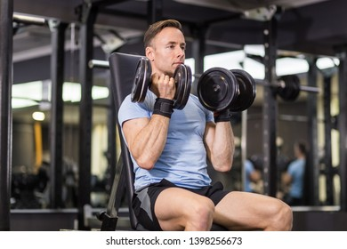 Muscular man doing exercise with dumbbell at the gym.