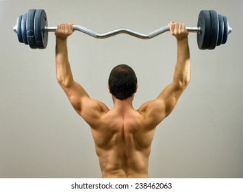 Muscular man doing exercises with barbell. Back view.