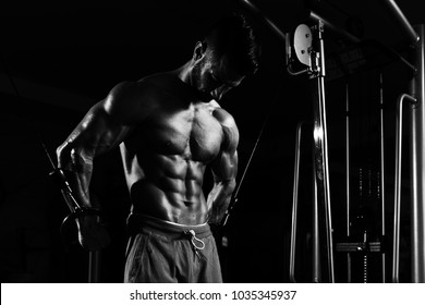 Muscular Man Doing Heavy Weight Exercise For Chest On Machine With Cable In The Gym