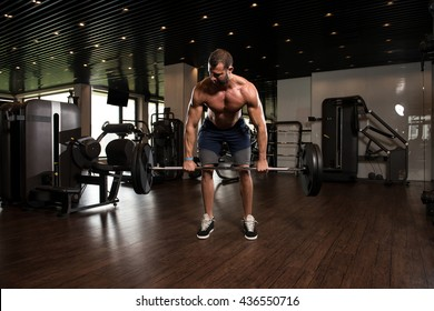 Muscular Man Doing Heavy Weight Exercise For Back With Barbell In Modern Gym