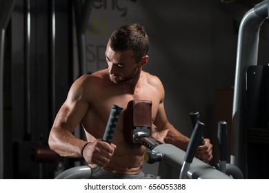 Muscular Man Doing Heavy Weight Exercise For Back On Machine