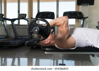 Muscular Man Doing Heavy Weight Exercise For Triceps With Barbell In Gym
