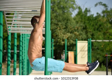 Muscular Man Doing Pull Ups On Horizontal Bar Outdoors.