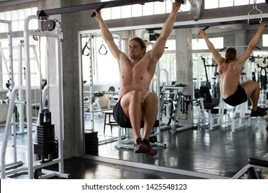 Muscular man doing pulling up on bar and pumping up  six pack abdominal at gym  .workout , exercises , bodybuilder training , sport .  hanging and  Raise legs