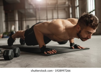 Muscular man doing push up exercise on mat near dumbbells during intense fitness workout in grungy gym