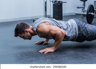 A muscular man doing a pushups at the crossfit gym