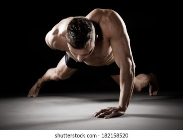 Muscular man doing push-ups on one hand against dark background.