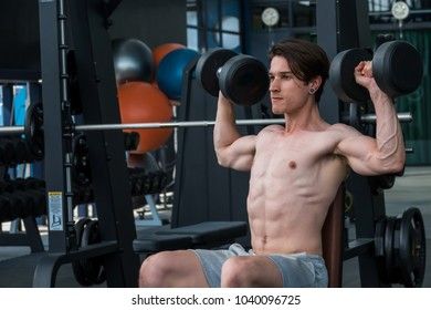 Muscular man doing some exercises  with gym equipment in fitness club. Shirtless sport man.