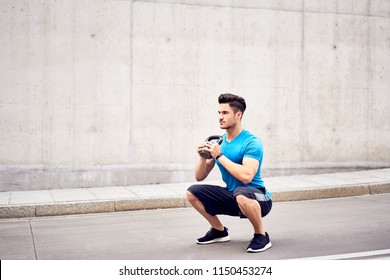 Muscular man doing squats with kettlebell in the city