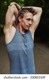 Muscular man doing stretching exercises raising his arms behind his head as he warms up before a training workout