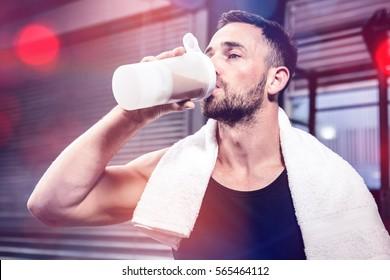 Muscular man drinking protein shake at crossfit gym