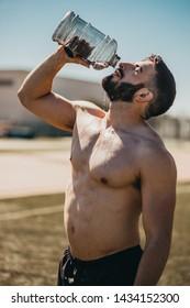 muscular man drinking water during training