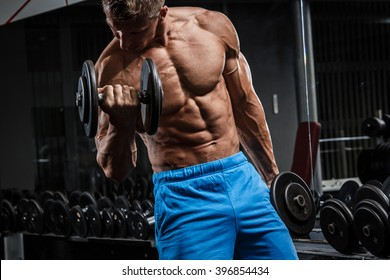Muscular man during workout in the gym