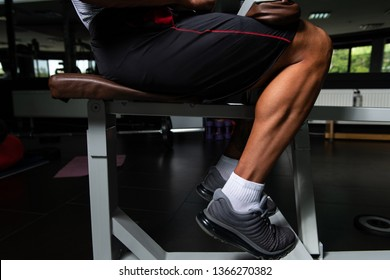 Muscular Man Exercising Calves On Machine In The Gym